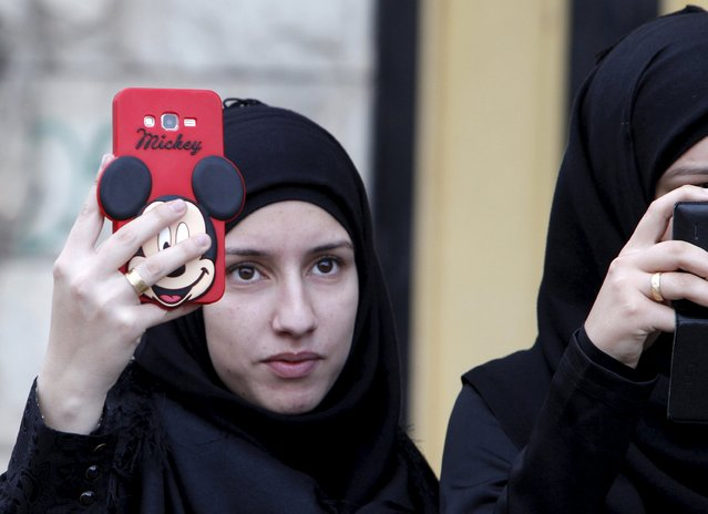 A woman takes pictures with her Mickey Mouse covered mobile phone as she attends the funeral of three Lebanon's Hezbollah fighters who were killed while fighting alongside Syrian army forces in Syria in Nabatieh town, southern Lebanon, October 27, 2015. (Photo by Ali Hashisho/Reuters)