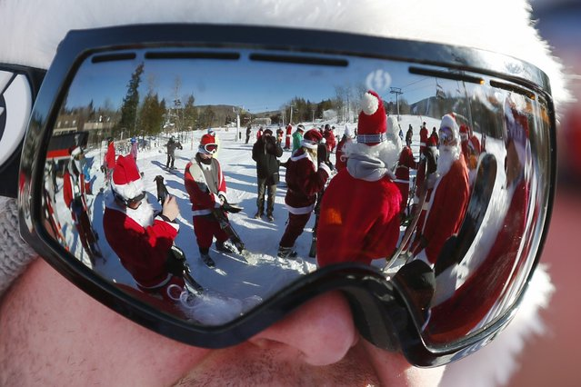 Skiers and snowboarders dressed as Santa Claus are reflected in a skier's goggles before participating in a charity run down a slope at Sunday River Ski Resort in Newry, Maine December 7, 2014. (Photo by Brian Snyder/Reuters)