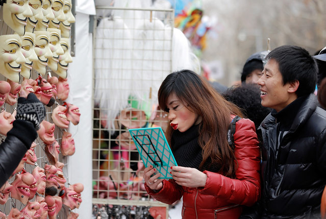 A woman tries on masks at a Spring Festival Temple Fair for celebrating Chinese Lunar New Year, on February 11, 2013 in Beijing, China. (Photo by Lintao Zhang /The Atlantic)