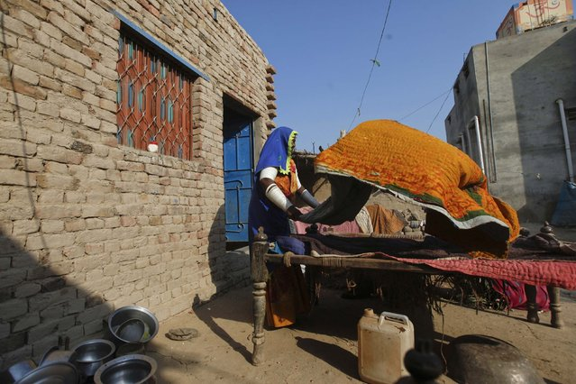 A woman cotton picker shakes the dust from bedding sheets in the sunshine outside her home in Meeran Pur village, north of Karachi November 23, 2014. (Photo by Akhtar Soomro/Reuters)