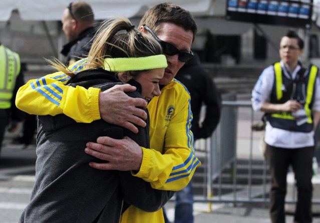 A woman is comforted by a man near a triage tent set up for the Boston Marathon after explosions went off at the 117th Boston Marathon in Boston, Massachusetts April 15, 2013. (Photo by Jessica Rinaldi/Reuters)