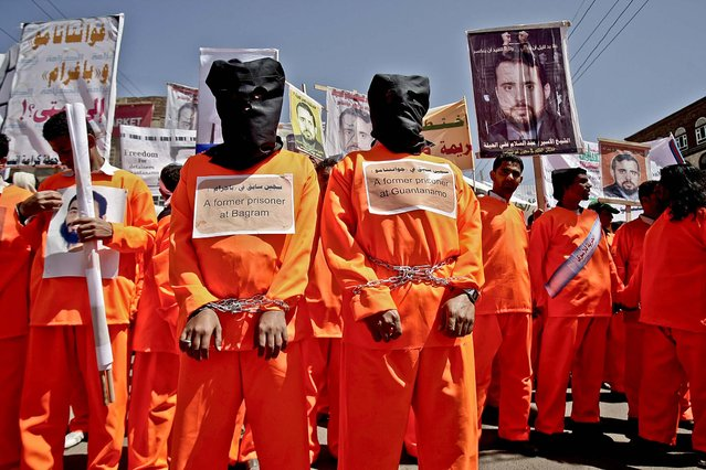 Former Bagram and Guantanamo Bay prisoners dressed in orange prison uniforms,demand the release of Yemeni detainees in the Guantanamo Bay prison as they protest in front of the US Embassy in Sanaa, Yemen, on April 16, 2013. (Photo by Hani Mohammed/Associated Press)