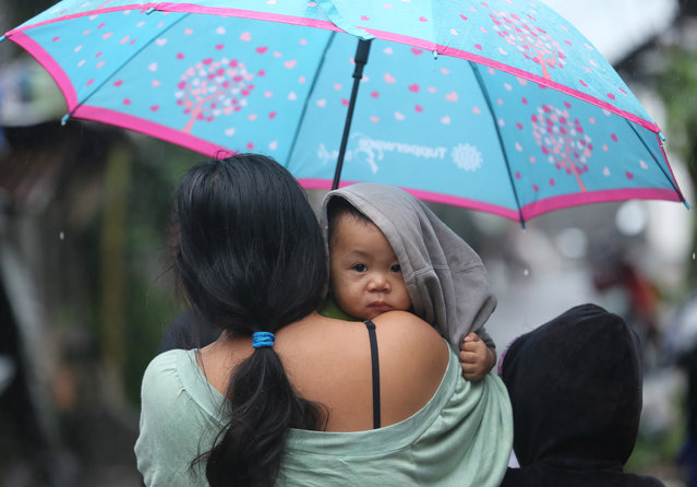 A young Filipino boy is carried by his mother as they return to their homes in Legazpi, Albay province, eastern Philippines on Monday, December 8, 2014 after strong waves from Typhoon Hagupit battered their coastal village last night. Typhoon Hagupit weakened into a tropical storm Monday after leaving at least 21 people dead and forcing more than a million people into shelters. (Photo by Aaron Favila/AP Photo)