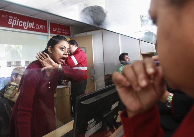 An employee of SpiceJet Airlines speaks with a passenger at the ticket counter at an airport on the outskirts of Agartala, capital of India's northeastern state of Tripura, December 17, 2014. The parent of India's SpiceJet Ltd said it can't afford to bail out the cash-strapped budget carrier that was forced to ground its entire fleet on Wednesday after creditor oil firms refused to refuel the aircraft. (Photo by Jayanta Dey/Reuters)