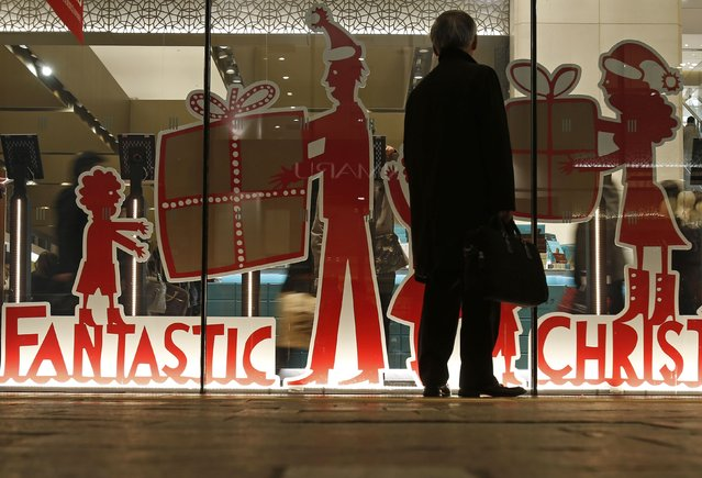 A man looks at a shop window with a decoration of a Christmas sale at a department store in Tokyo December 19, 2014. (Photo by Yuya Shino/Reuters)