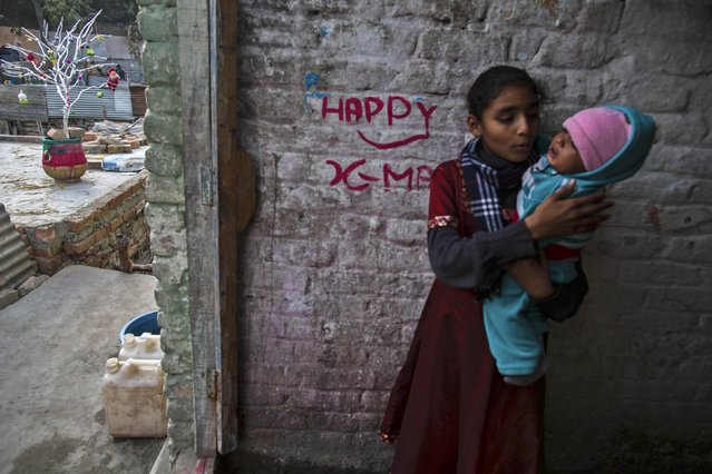 A girl carries her nephew at her house in a Christian slum in Islamabad on Christmas eve December 24, 2014. (Photo by Zohra Bensemra/Reuters)