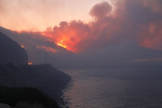 The Springs Fire burns in the early morning near Pacific Coast Highway at Point Mugu State Park, May 3, 2013. A wind-driven wildfire raging along the California coast north of Los Angeles prompted the evacuation of hundreds of homes and a university campus on Thursday as flames engulfed several farm buildings and recreational vehicles near threatened neighborhoods. (Photo by Jonathan Alcorn/Reuters)