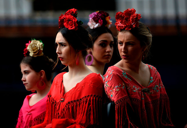 """Participants sporting Andalusian traditional dresses wait for parading in the XXXIII """"Enganches"""" (Horse- drawn carriages) exhibition at the Real Maestranza bullring in Sevilla on April 15, 2018. (Photo by Cristina Quicler/AFP Photo)"""