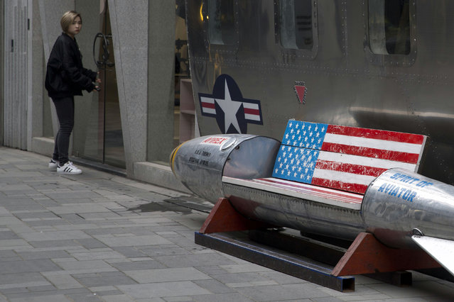 In this March 23, 2018, photo, a woman tries to open a door near an advertising gimmick in the shape of a bomb with a U.S. flag outside a U.S. apparel store in Beijing, China. President Donald Trump's threat to hike tariffs on technology imports from China strikes at the heart of Beijing's state-led blueprint for prosperity and restoring the nation's greatness. (Photo by Ng Han Guan/AP Photo)