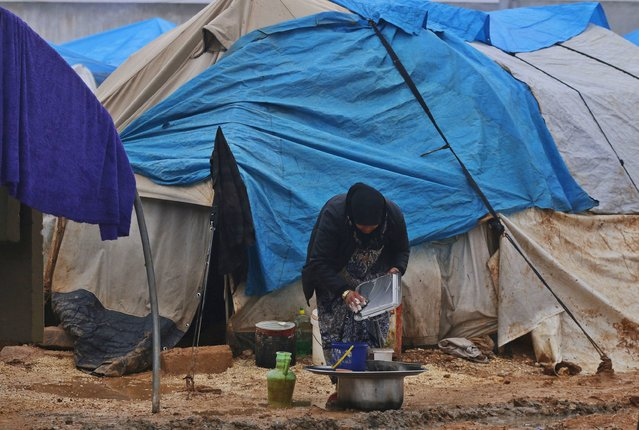 An internally displaced woman washes dishes outside tents at the Bab Al-Salam refugee camp in Azaz, near the Syrian-Turkish border December 28, 2014. (Photo by Hosam Katan/Reuters)