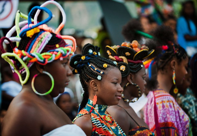 Girls present African-Colombian hairstyles during the 9th contest of Afro-hairdressers, in Cali, Valle del Cauca departament, Colombia, on May 12, 2013. The Afro hairstyles have their origins in the time of slavery, when women sat to comb their children hair after work. (Photo by Luis Robayo/AFP Photo)