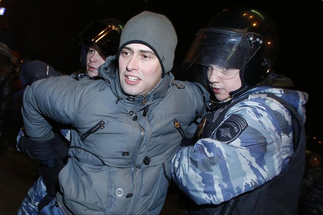 Police officers detain a protester during unsanctioned protest in Moscow, Russia, Tuesday, December 30, 2014. (Photo by Denis Tyrin/AP Photo)
