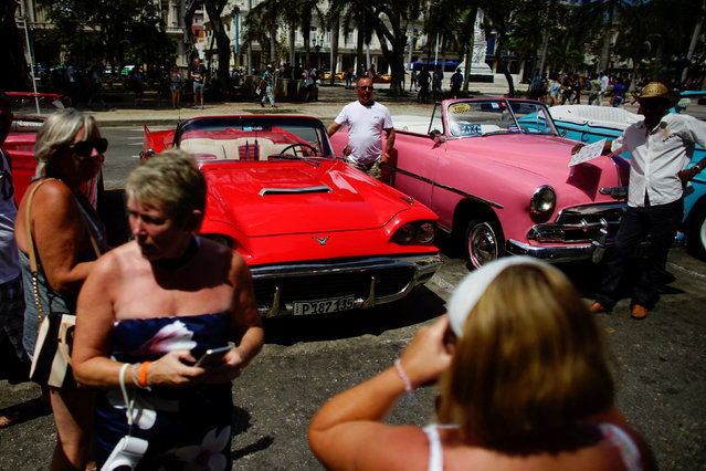 Tourists take photos beside vintage cars in Havana, Cuba, September 12, 2017. Picture taken September 12, 2017. (Photo by Alexandre Meneghini/Reuters)