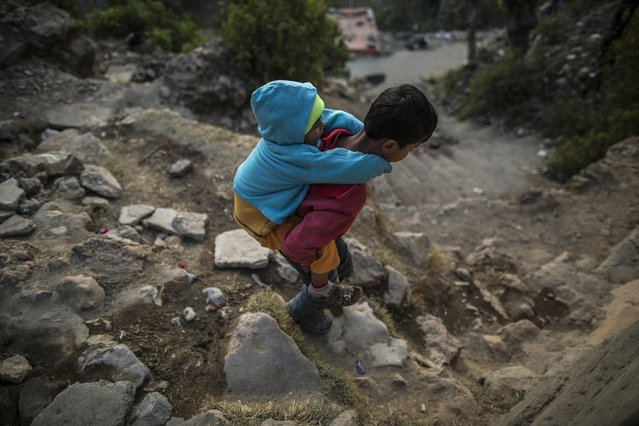 A boy carries his sibling as he walks to Saidpur village in Islamabad January 6, 2015. (Photo by Zohra Bensemra/Reuters)