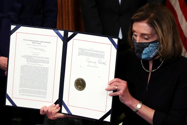U.S. House Speaker Nancy Pelosi (D-CA) shows the article of impeachment against U.S. President Donald Trump after signing it in an engrossment ceremony, at the U.S. Capitol in Washington on January 13, 2021. (Photo by Leah Millis/Reuters)