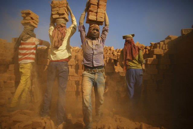 Workers carry bricks by balancing them on their heads at a brick factory in Lalitpur January 12, 2015. (Photo by Navesh Chitrakar/Reuters)