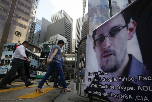 People walk past a banner supporting Edward Snowden, a former CIA employee who leaked top-secret documents about sweeping U.S. surveillance programs, at Central, Hong Kong's business district, Monday, June 17, 2013. Top officials from the Obama and Bush administrations say the government's newly exposed secret surveillance programs have been essential to disrupting terrorist plots and have not infringed on Americans' civil liberties. (Photo by AP Photo)