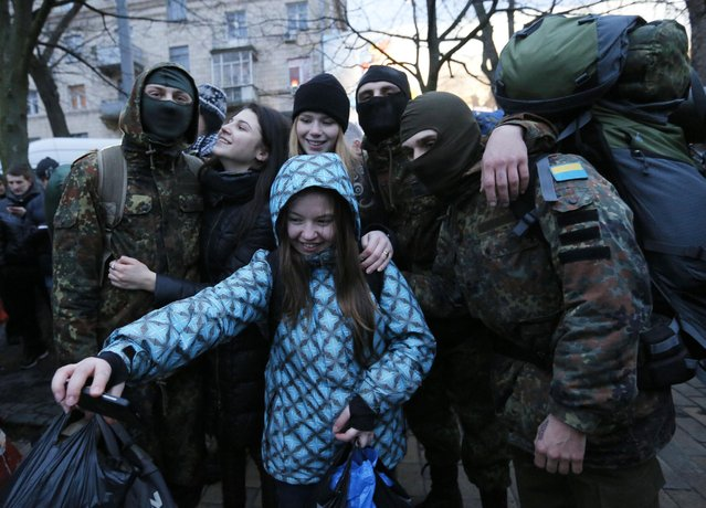 """Volunteers being photographed with friends before being sent to the eastern part of Ukraine to join the ranks of special battalion """"Azov"""" fighting against pro-Russian separatists, in Kiev, Ukraine, Saturday, January 17, 2015. (Photo by Sergei Chuzavkov/AP Photo)"""