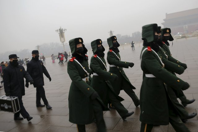 "Paramilitary policemen wearing masks march on a cold morning following a flag-raising ceremony amid heavy smog at Tiananmen Square, after the city issued its first ever ""red alert"" for air pollution, in Beijing December 9, 2015. (Photo by Damir Sagolj/Reuters)"