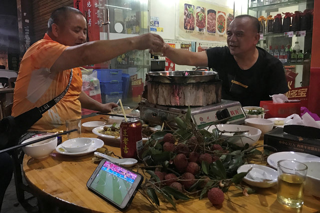 Customers toast as they watching the World Cup 2018 match, over a dog meat dish at a dog meat market ahead of a local dog meat festival in Yulin, Guangxi Zhuang Autonomous Region, China on June 21, 2018. (Photo by Tyrone Siu/Reuters)