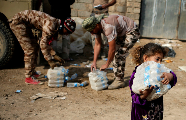 A girl carries bottles of water given by Iraqi soldiers in a village outside Mosul, Iraq November 9, 2016. (Photo by Goran Tomasevic/Reuters)