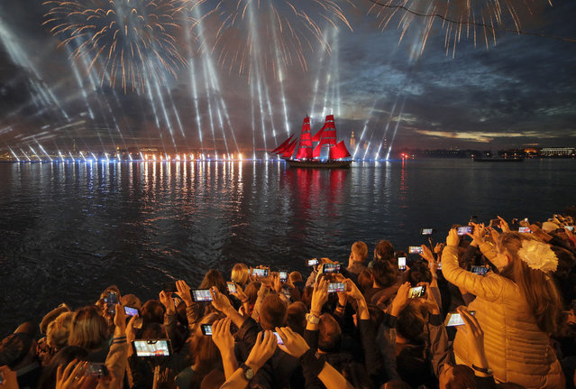People watch a brig with scarlet sails on the Neva River during the Scarlet Sails festivities marking school graduation in St. Petersburg, Russia, early Sunday, June 24, 2018. This week graduation ceremonies and celebrations are held all over Russia as students of elementary and high schools and military academies finished their education. (Photo by Dmitri Lovetsky/AP Photo)