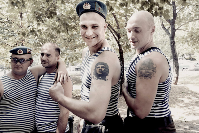 Two young soldiers show off their tattooed arms. (Photo by Aude Osnowycz/The Guardian)