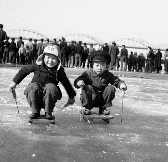 Two Seoul youngsters have fun on the Han River ice with their home-made, single-sleds, called a solme on February 23, 1959. The sleds are made of small pieces of wooden board with two or three pieces of iron bar beneath.The Han River in South Korea, once the scene of underscribable tragedy during the Korean War, is now a recreational spot for youngsters during the winter months. There they skate and frolic. During the summer it becomes a swimming place. The bridge, which once bore ugly scars of war, has now been completely rebuilt to give the river an inspiring background. Twice during the war, thousands of South Koreans crossed the river, which runs through the southern part of Seoul, the capital, to take refuge in the south from Communist invasion. (Photo by Kim Chon Kil/AP Photo)