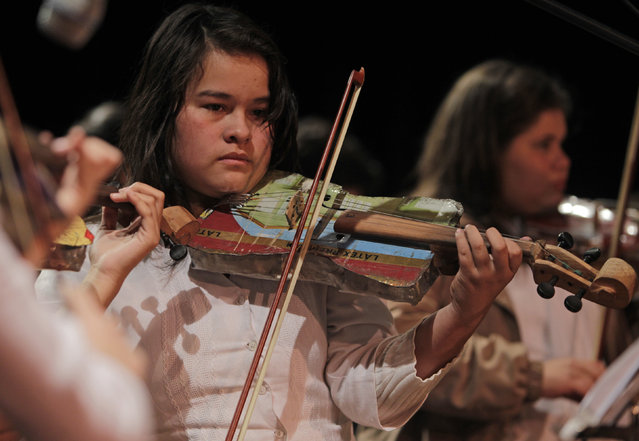Music student Valencia plays a violin made from recycled objects during a concert of the Orchestra of Recycled Instruments of Cateura, in Asuncion, June 22, 2013. The orchestra is the brainchild of its conductor Favio Chavez, who wanted to help the children of garbage pickers at the local landfill, and the instruments are made from salvaged materials by craftsman Nicolas Gomez. (Photo by Jorge Adorno/Reuters)