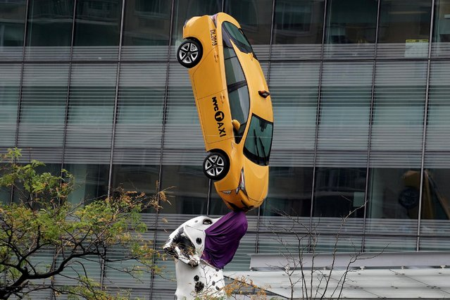 """A sculpture called """"Dalmation"""" balances a taxi on its nose while wearing a face covering during the coronavirus disease (COVID-19) pandemic in the Manhattan borough of New York City, New York, U.S., November 13, 2020. (Photo by Carlo Allegri/Reuters)"""