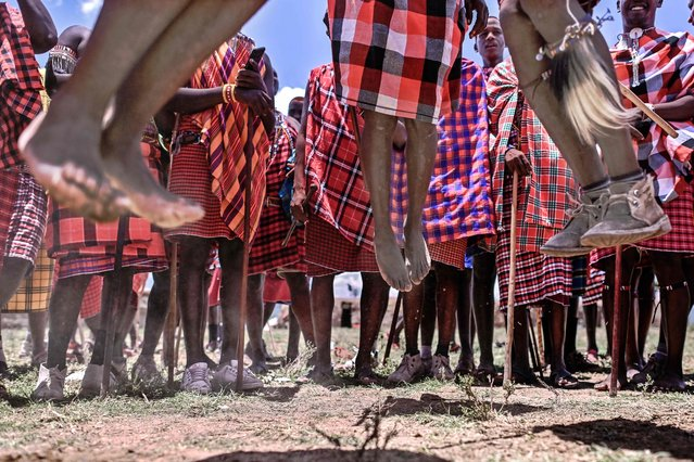 Men from the Kenyan Maasai tribe perform a traditional jumping-ritual among fellow members of a common age-set as they observe a rite of passage to mark the transition of an age-set to cultural junior elder from Moran (Maasai for warrior age-set) at a manyatta or traditional homestead built specifically for the ceremony near Lemek town within the Masai-Mara National Reserve ecosystem in Narok county February 27, 2021. (Photo by Tony Karumba/AFP Photo)
