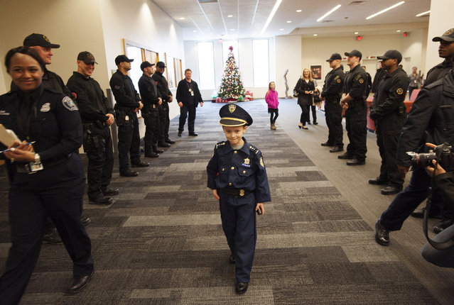 "Detroit Police ""Chief for a Day"" Carter Widmer, 7, arrives at the Detroit Public Safety Headquarters on Wednesday, December 23, 2015, in Detroit. Widmer donated $250 of his Christmas money to the Detroit Police K-9 Unit. (Photo by John T. Greilick/Detroit News via AP Photo)"