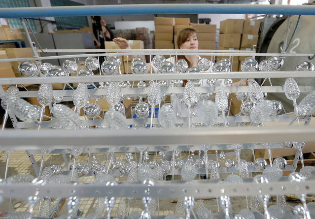 """An employee adjusts glass spheres for Christmas and New Year decorations before coating them with a layer of aluminum at the """"Yolochka"""" (Christmas tree) factory, which has been producing glass decorations and toys for the festive season since 1848, in the town of Klin outside Moscow, Russia, November 24, 2016. (Photo by Maxim Zmeyev/Reuters)"""