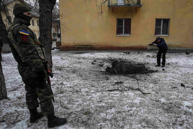 A Ukrainian serviceman guards the street next to the remains of a rocket shell in the town of Kramatorsk, eastern Ukraine February 10, 2015. (Photo by Gleb Garanich/Reuters)