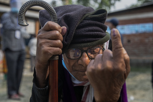 An elderly tribal Mishing man Lakkhi Payeng, 112, displays the indelible ink on his finger after casting his vote during the first phase of Assam state elections in Majuli, India, Saturday, March 27, 2021. (Photo by Anupam Nath/AP Photo)