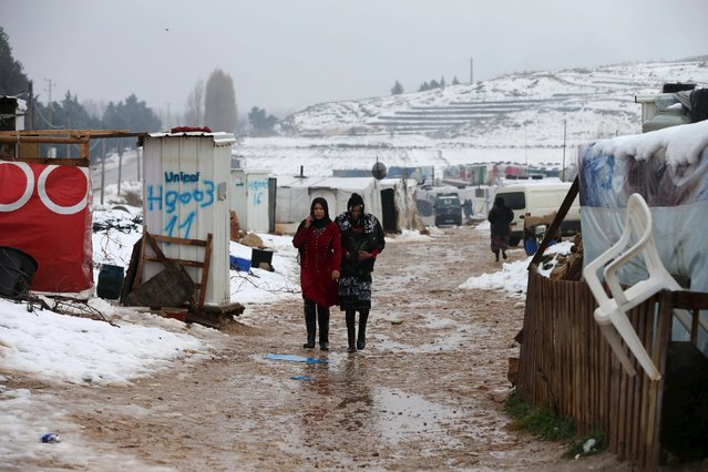 Two Syrian women from Raqqa walk through a Syrian refugee camp in the Bekaa Valley in Lebanon after the first heavy snow storm hit Lebanon, January 3, 2016. (Photo by Jamal Saidi/Reuters)