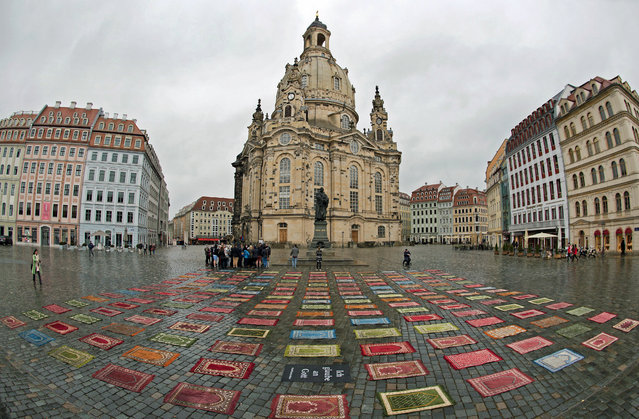 175 Muslim prayer rugs lie in front of the Frauenkirche in Dresden, Germany, 09 February 2015. German artist Kurt Fleckenstein placed the rugs in front of the church just a few hours before a planned rally of the anti-Islam movement Pegida (Patriotic Europeans Against the Islamization of the West). Fleckenstein wants to take a stand against Pegida for more tolerance. (Photo by Arno Burgi/EPA)