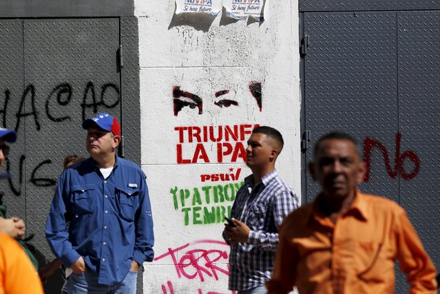 Supporters of Venezuela's President Nicolas Maduro stand in front of a graffiti of the eyes of Venezuela's late President Hugo Chavez some streets away from the building housing the National Assembly in Caracas, January 5, 2016. (Photo by Marco Bello/Reuters)