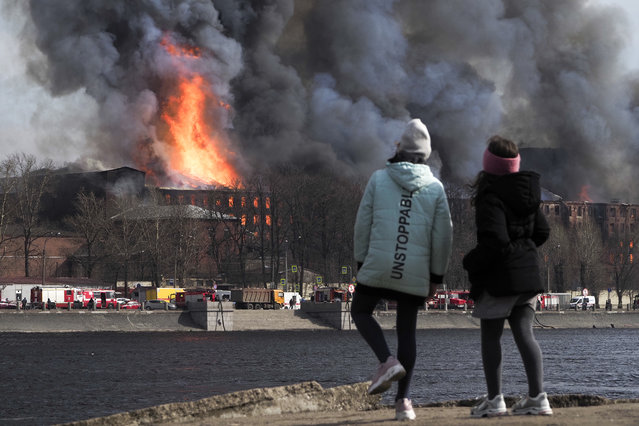 People look at smoke and flame rising from the Nevskaya Manufaktura textile factory founded by English merchant J. Thornton in 1841, in St. Petersburg, Russia, Monday, April 12, 2021. The emergencies ministry said the fire had broken out over several floors of the red-brick Nevskaya Manufaktura building on the Oktyabrskaya Embankment of the Neva River. (Photo by Dmitri Lovetsky/AP Photo)