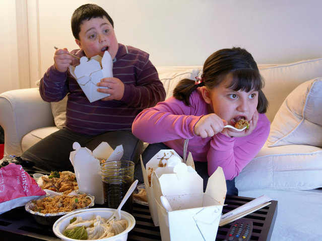 Overweight brother and sister sitting side by side on a sofa eating takeaway food and watching the TV. (Photo by Digital Vision/Getty Images)