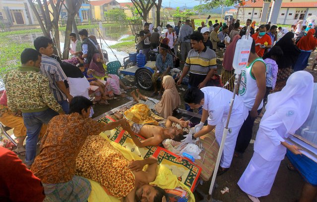Earthquake survivors receive medical treatment outside a district hospital overloaded with patients in Pidie Jaya, Aceh province, December 7, 2016. (Photo by Aqien Abdullah/AFP Photo)