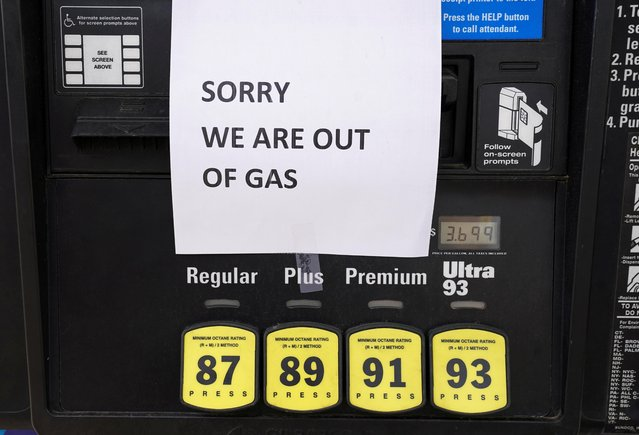 A sign tells drivers that gas pumps are empty as stations from Florida to Virginia began running dry and prices at the pump rose as the shutdown of the Colonial Pipeline by hackers sparked panic buying by motorists, in Falls Church, Virginia, May 12, 2021. (Photo by Kevin Lamarque/Reuters)