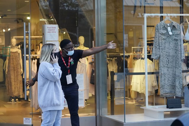A salesperson gives directions to a shopper amid the COVID-19 pandemic on The Promenade Wednesday, June 9, 2021, in Santa Monica, Calif. (Photo by Marcio Jose Sanchez/AP Photo)