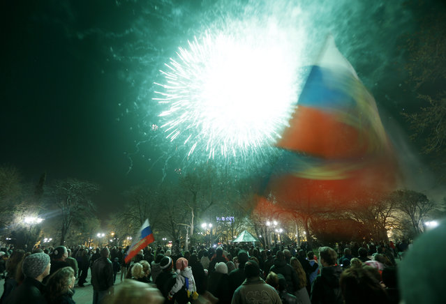People watch fireworks and wave Russian flags in Sevastopol, March 21, 2014. (Photo by Vasily Fedosenko/Reuters)