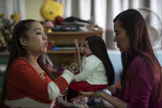 "Mananya Boonmee (L), 49, performs a ritual on a ""child angel"" doll and her owner Manita Chuenarom (R), 33, at her house in Nonthaburi, Thailand, January 26, 2016. (Photo by Athit Perawongmetha/Reuters)"