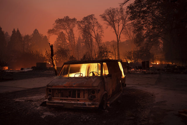 Flames burn inside a van as the Camp Fire tears through Paradise, Calif., on Thursday, November 8, 2018. Tens of thousands of people fled a fast-moving wildfire Thursday in Northern California, some clutching babies and pets as they abandoned vehicles and struck out on foot ahead of the flames that forced the evacuation of an entire town and destroyed hundreds of structures. (Photo by Noah Berger/AP Photo)