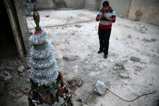 Akram Abu al-Foz takes a picture of a Christmas tree he decorated from empty shells which he collected and painted on, in the rebel held besieged city of Douma, in the eastern Damascus suburb of Ghouta, Syria December 23, 2016. (Photo by Bassam Khabieh/Reuters)