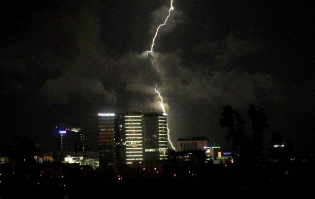 A lightning strikes over buildings as a thunderstorm passes through Prague, Czech Republic, June 29, 2021. (Photo by David W. Cerny/Reuters)