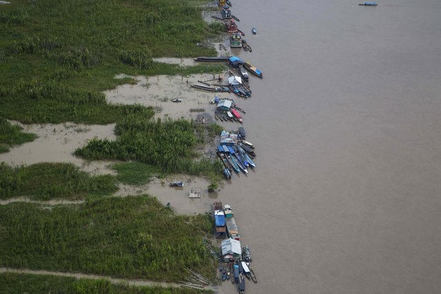 This March 16, 2015 photo shows small boats anchored along the shore of the Ucayali River near Pucallpa, Peru. Illegal logging persists unabated in this remote Amazon community where four indigenous leaders who resisted it were slain in September. The leaders campaigned for more than a decade for title to the community's ancestral tract bordering Brazil. (Photo by Martin Mejia/AP Photo)