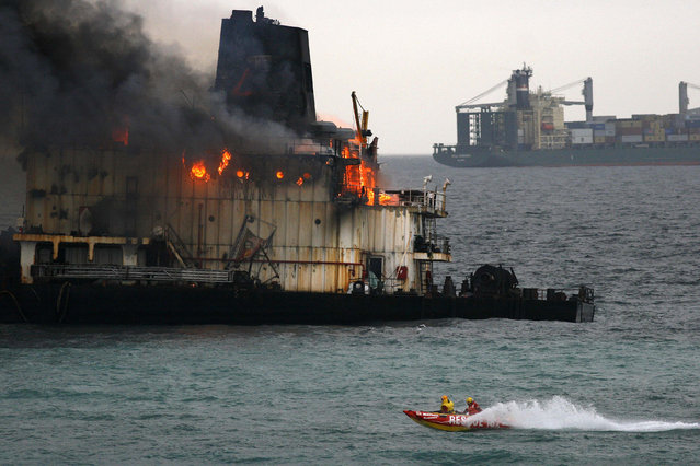 Sea Rescue boats monitor the stranded bulk coal carrier Seli 1 as it burns off Cape Town's Blouberg beach, South Africa, June 3, 2010. (Photo by Mark Wessels/Reuters)